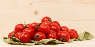 Tomaten auf hölzernem Hintergrund des grünen Gewebes Lizenzfreie Stockbilder