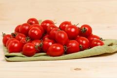 Tomaten auf hölzernem Hintergrund des grünen Gewebes Stockfoto