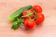 Tomaten auf Niederlassung, Gurke und Petersilie auf einer Holzoberfläche Lizenzfreies Stockfoto
