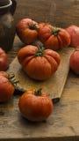 Tomaten auf rustikalem hölzernem hackendem Brett und Holztisch Stockfoto