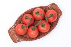 Tomaten in een mand worden geïsoleerd die stock afbeelding