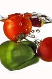 Tomaten en groene paprika die in water worden gelaten vallen Stock Afbeeldingen