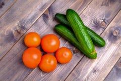 Tomaten en komkommers op de houten achtergrond Stock Fotografie