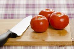 Tomaten en mes op scherpe raad. Royalty-vrije Stock Afbeelding