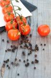 Tomaten en peperbollen op houten lijst Royalty-vrije Stock Foto's