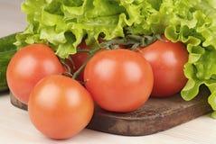 Tomaten en salade op scherpe raad Stock Afbeelding