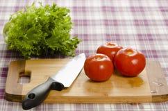 Tomaten en sla op lijst met hakbord en mes. stock foto's