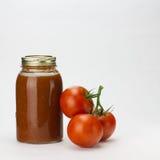 Tomaten en tomatensaus op wit Stock Afbeelding