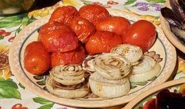 Tomaten en uien op een ceramische plaat worden en worden gelegd geroosterd die royalty-vrije stock foto
