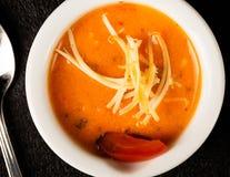 Tomaten-Fischcremesuppen-Suppe in der weißen Schüssel und im Löffel Stockfotos
