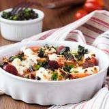 Tomaten gebacken mit Käsefeta, geräucherte Würste, Kräuter, Oliven Lizenzfreie Stockfotos
