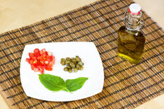 Tomaten, Kapriolen und Basilikum auf einer weißen Platte und einem Olivenöl Stockfotos