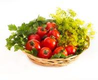 Tomaten mit Petersilie in der Weidenplatte Lizenzfreie Stockfotografie
