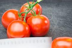 Tomaten op scherpe raad met mes Royalty-vrije Stock Foto's