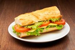 Tomaten, ost och sallad skjuter in från den nya bagetten på den vita keramiska plattan på den mörka trätabellen Arkivfoton