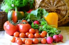 Tomaten, radijzen, peper en peterselie op houten hakbord Stock Afbeelding