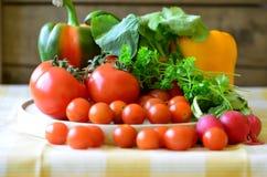 Tomaten, radijzen, peper en peterselie op houten hakbord Stock Foto