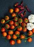 Tomaten, roter Pfeffer und Knoblauch gegen einen dunklen Hintergrund Stockfotos