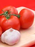 Tomaten u. Knoblauch auf Rot Stockfotografie