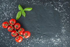 Tomaten und Basilikum auf schwarzem Stein mit Salz Stockfoto