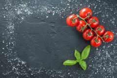 Tomaten und Basilikum auf schwarzem Stein mit Salz Stockfotografie