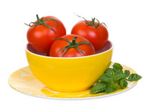 Tomaten und Basilikum in der gelben Schüssel und in der Platte Stockfotografie