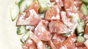 Tomaten- und Gurkensalat mit Grüns drehen sich stock footage