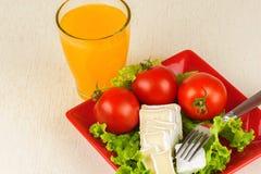 Tomaten und Käsescheiben liegen auf einem Blatt des frischen Salats in einer roten Platte Stockfoto
