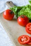 Tomaten und Kopfsalat auf einem hölzernen Hintergrund Stockfoto