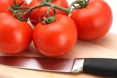 Tomaten und Messer Stockfotografie