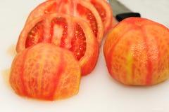 Tomaten und Messer auf weißem Hintergrund Stockfotografie