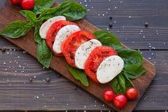 Tomaten- und Mozzarellascheiben mit Basilikumblättern Stockfotografie
