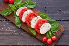 Tomaten- und Mozzarellascheiben mit Basilikumblättern Stockfotos