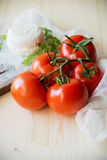 Tomatenniederlassung auf hölzerner Tabelle der Weinlese - ländliches Stillleben von oben, neue Ernte vom Garten Stockfoto