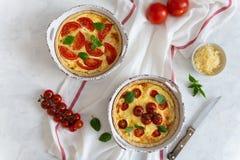 Tomatenpastei met basilicumbladeren, kippenans kaas op wit tafelkleed Eigengemaakte Franse quiche Hoogste mening, exemplaarruimte stock afbeelding