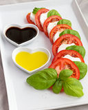 Tomatenplakken, basilicum en geitkaas met olie en azijn Stock Foto