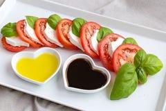 Tomatenplakken, basilicum en geitkaas met olie en azijn Royalty-vrije Stock Foto