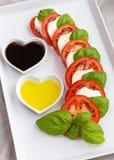 Tomatenplakken, basilicum en geitkaas met olie en azijn Royalty-vrije Stock Afbeelding
