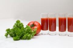 Tomatensaft in einem Glas mit Tomaten und Petersilie strahlen Stockfoto