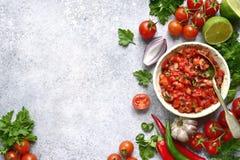 Tomatensalsa-Salsa roja - traditionelle mexikanische Soße mit Bestandteilen für die Herstellung auf einem hellgrauen Schiefer, St stockfoto