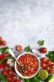 Tomatensalsa-Salsa roja - traditionelle mexikanische Soße mit Bestandteilen für die Herstellung auf einem hellgrauen Schiefer, St stockbild