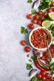 Tomatensalsa-Salsa roja - traditionelle mexikanische Soße mit Bestandteilen für die Herstellung auf einem hellgrauen Schiefer, St lizenzfreies stockfoto