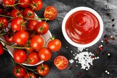 Tomatensauce in den weißen Schüssel-, Gewürz- und Kirschtomaten auf einer Dunkelheit Lizenzfreie Stockfotografie