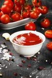 Tomatensauce in den weißen Schüssel-, Gewürz- und Kirschtomaten auf einer Dunkelheit Stockbild