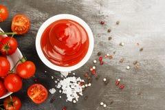 Tomatensauce in den weißen Schüssel-, Gewürz- und Kirschtomaten auf einer Dunkelheit Lizenzfreies Stockfoto