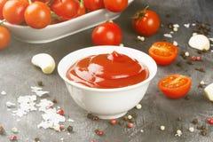 Tomatensauce in den weißen Schüssel-, Gewürz- und Kirschtomaten auf einer Dunkelheit Stockfotografie