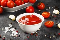 Tomatensauce in den weißen Schüssel-, Gewürz- und Kirschtomaten auf einer Dunkelheit Stockfoto