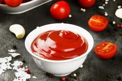 Tomatensauce in den weißen Schüssel-, Gewürz- und Kirschtomaten auf einer Dunkelheit Stockfotos