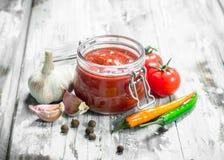 Tomatensauce in einem Glas und in den Gewürzen lizenzfreies stockbild