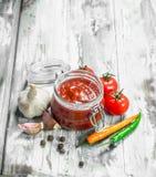 Tomatensauce in einem Glas und in den Gewürzen lizenzfreies stockfoto